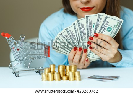 Woman holding cash, and on the table are coins, credit card and the shopping cart - online shopping concept