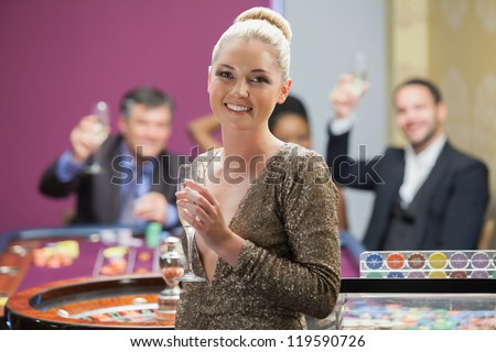 Woman holding champagne glass as people are cheering behind her in casino - stock photo