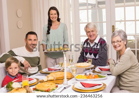 Woman holding christmas dinner with family at dinning table at home in the living room