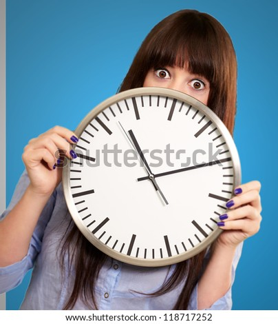 Woman Holding Clock Isolated On Blue Background - stock photo