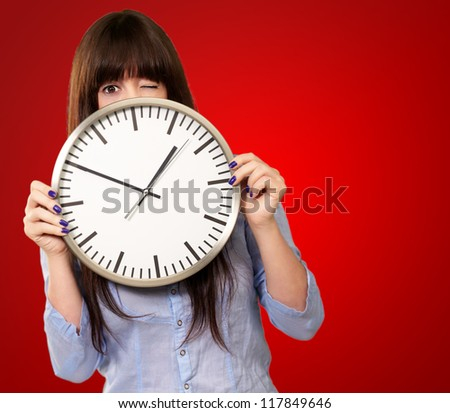 Woman Holding Clock Winking Isolated On Red Background