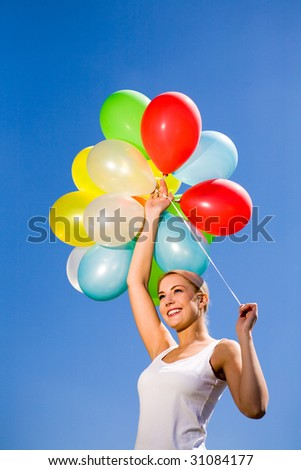 Woman holding colored balloons against blue sky