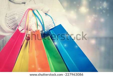 Woman holding colorful shopping bags in snowy night - stock photo
