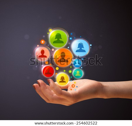 Woman holding colorful social network icons in her hand - stock photo