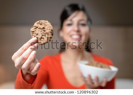 Woman holding cookie. Night scene with hungry cheerful brunette caucasian girl in bedroom. - stock photo