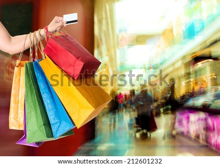 Woman holding credit card and shopping bags at shopping mall