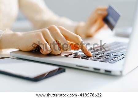 Woman holding credit card in hand and entering security code using laptop keyboard, photo with depth of field - stock photo
