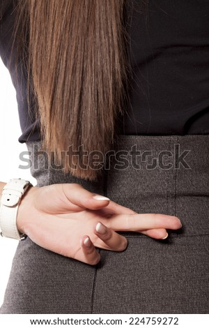 woman holding crossed fingers behind her back - stock photo