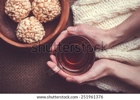 Woman holding cup of black tea on white woollens and rice crispy balls in wooden bowl - stock photo