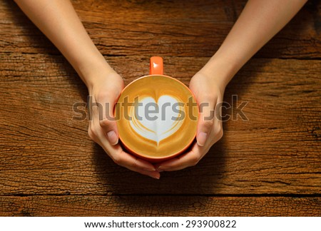 Woman holding cup of coffee latte, with heart shape - stock photo