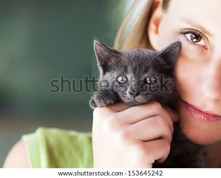Woman holding cute black kitten - stock photo