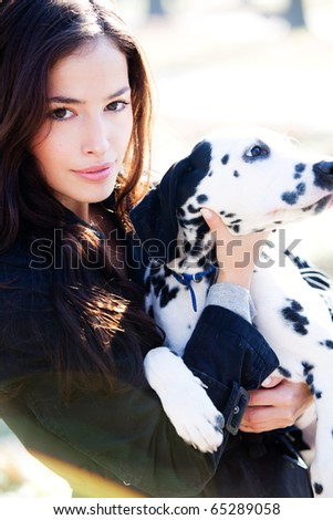 woman holding dalmatian puppy, outdoor shot