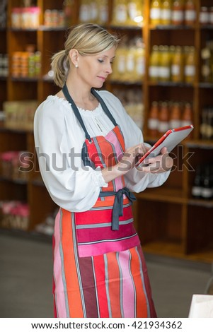 Woman Holding Digital Tablet In Grocery Store - stock photo