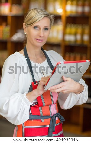 Woman Holding Digital Tablet In supermarket