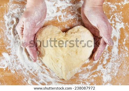 Woman holding dough heart in his hands - stock photo
