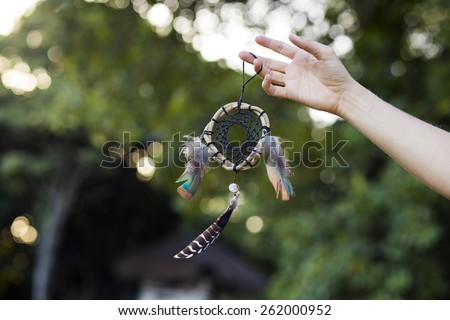 Woman holding dream catcher in nature - stock photo