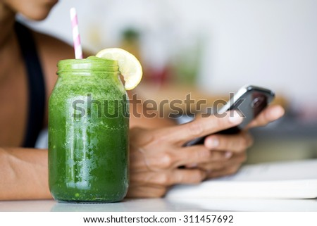 Woman holding electronic tablet while drinking a green detox juice. - stock photo