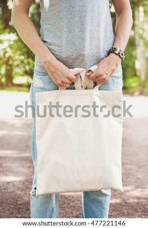 Woman holding empty canvas bag outdoor. Template mock up