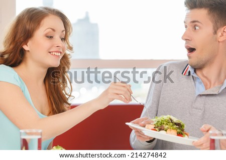 woman holding fork and eating man's salad. man holding plate with salad and moving away - stock photo