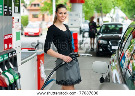 woman holding fuel nozzle in gas station - stock photo