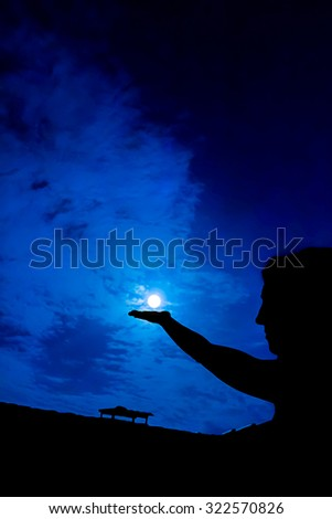 Woman holding full moon in hand against night sky - stock photo