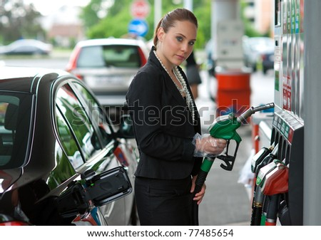 woman holding gas nozzle in gas station - stock photo