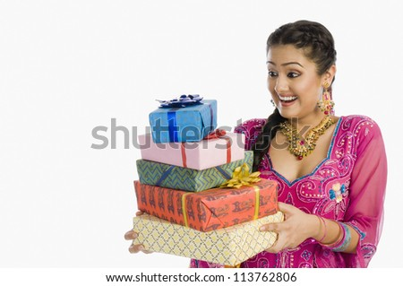 Woman holding gifts and smiling - stock photo