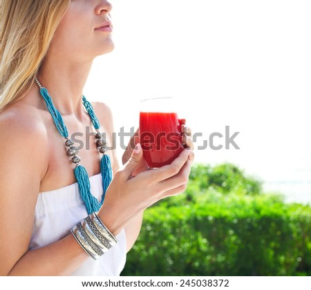 Woman holding glass of a strawberry juice in her hand hand - stock photo