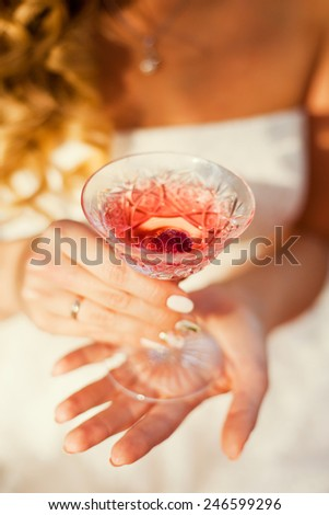 woman holding glass of pink wine - stock photo