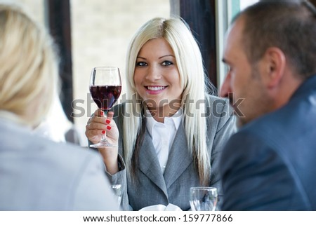 woman holding glass of red wine and toasting