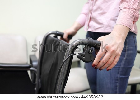 woman holding handles of wheelchair in lobby of hospital ready to transport patient - stock photo