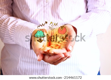 woman holding hands in cupped shape and drawings of charts and infographics. Close up image with selective focus. Business concept.   - stock photo