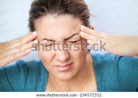 Woman holding hands on her head, depression, pain, migraine - stock photo