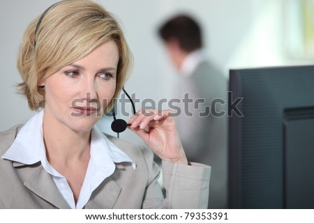 Woman holding headset at computer.