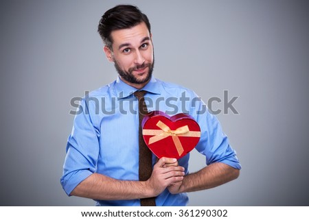 Woman holding heart-shaped box - stock photo