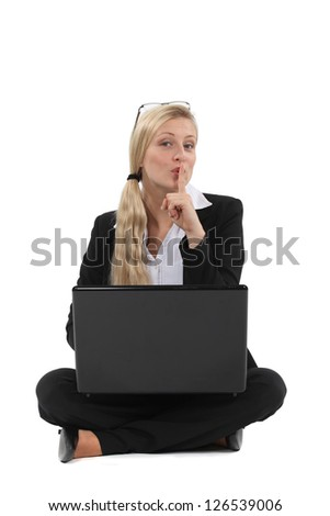 Woman holding her finger to her lips - stock photo