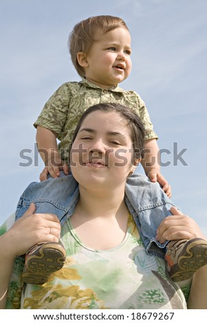 Woman holding her little child on back