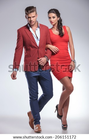 woman holding her man by arm and both posing in studio - stock photo