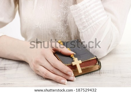 Woman holding Holy Bible and wooden rosary - stock photo