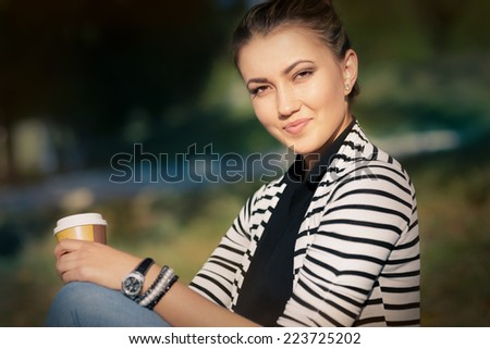Woman holding hot beverage enjoying nature - Portrait of a woman relaxing outside  - stock photo