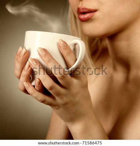 woman holding hot cup and blowing on it - stock photo