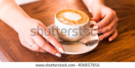 woman holding hot cup of coffee, with heart shape - stock photo