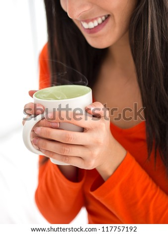 Woman holding hot cup of steaming coffee with two hands. - stock photo
