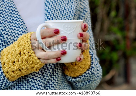 Woman holding hot cup with two hands - stock photo