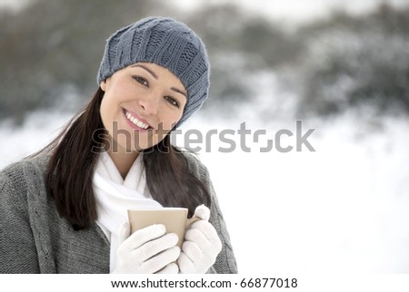 Woman holding hot drink outside in the snow - stock photo
