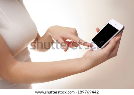 Woman holding in her hand cell phone and touching the button - stock photo