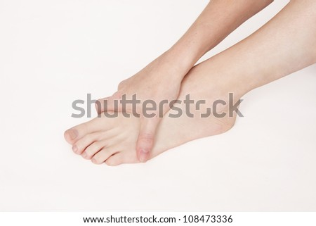 Woman holding injured foot - stock photo