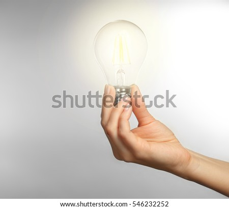 Woman holding light bulb on light background
