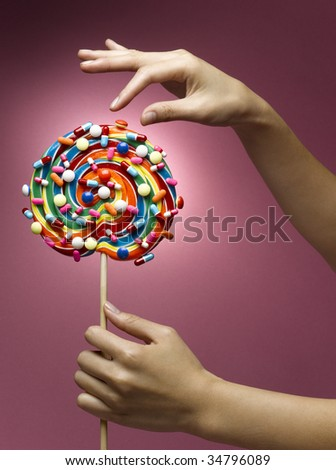 Woman holding lollipop decorated with pills, close-up of hands - stock photo