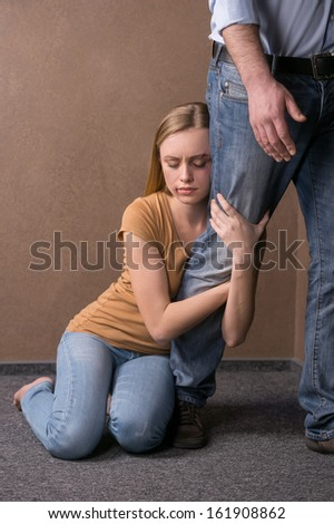 Woman holding man by his leg. Preventing from going away  - stock photo